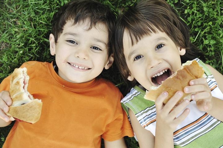 дети лежат на траве и едят