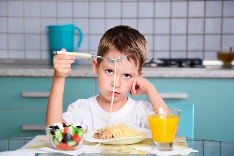 мальчик ест макароны