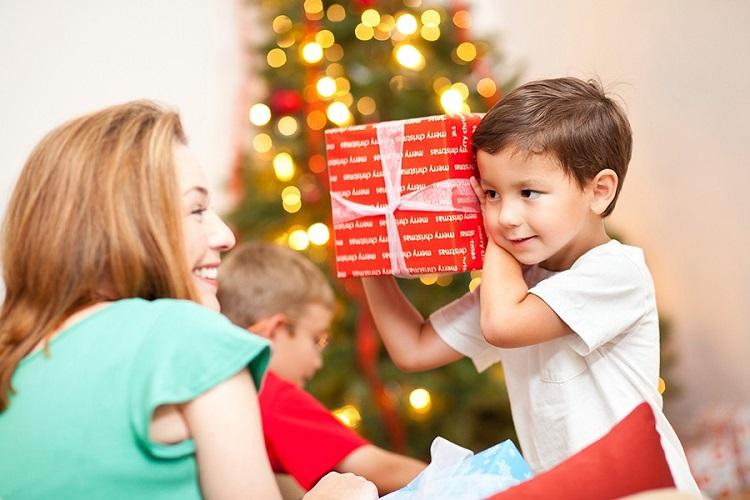 мама дарит подарок ребенку на новый год