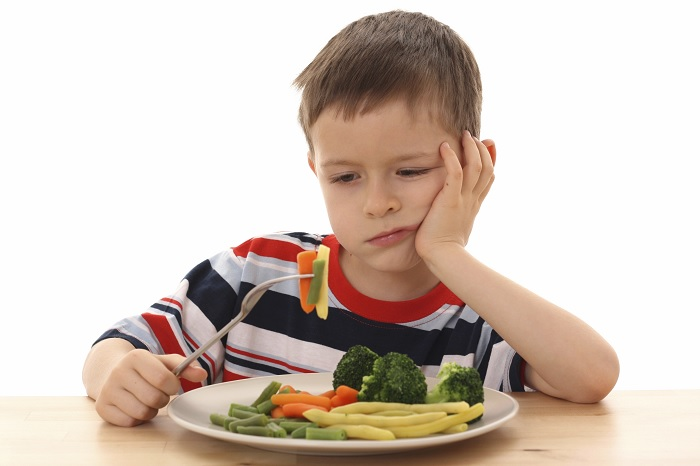 ребенок и тарелка овощей